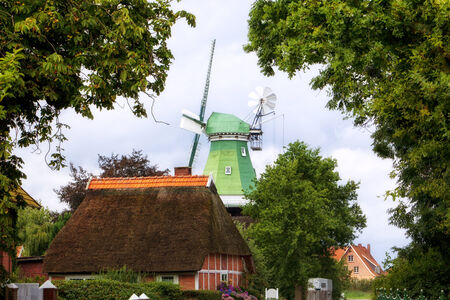 half timbered house: Thatch roof cottage and old windmill at Altes Land, Germany
