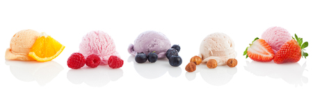 five scoops of ice cream and sorbet arranged with the fruits they are made of isolated on white background