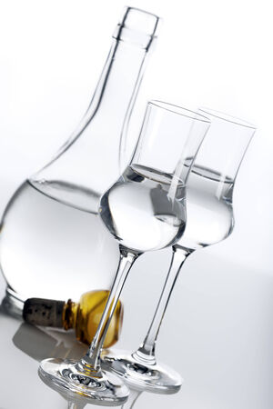 tilted view: Clear spirit in two glasses and carafe, tilted view Stock Photo
