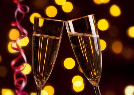 Two glasses of champagne, bright lights and streamers