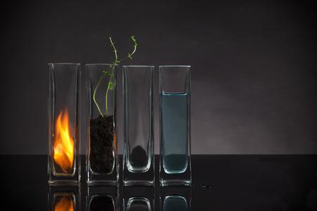 four elements: Los cuatro elementos - fuego, tierra, aire y agua dispuestos en jarrones de cristal