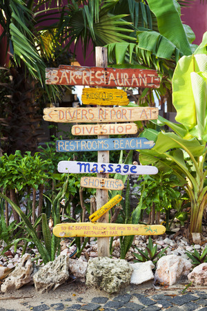 Signpost made of flotsam at tropical resort showing directions to facilities at beach Stock Photo