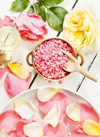 bath essence: pink and yellow roses petals bath salt aromatic essence top view wood background Stock Photo
