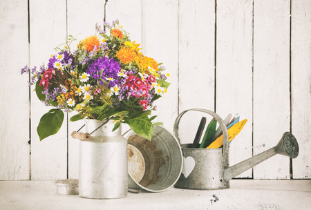 Flower bouquet in old milk churn tin bucket and watering can. Vintage processing with dust and scratches.