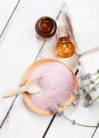 Wooden bowl of bath salt with flowers towels apothecary bottle