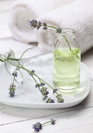 essence: Lavender flowers in bottle with essence towels in background