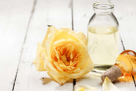 Yellow rose blossom and bottle of extract on rustic background Stock Photo