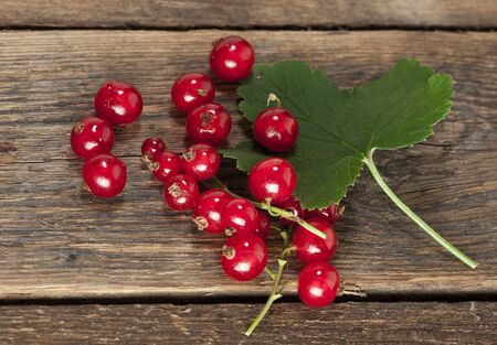 redcurrant: ripe redcurrant with leaf on rustic wooden background Stock Photo