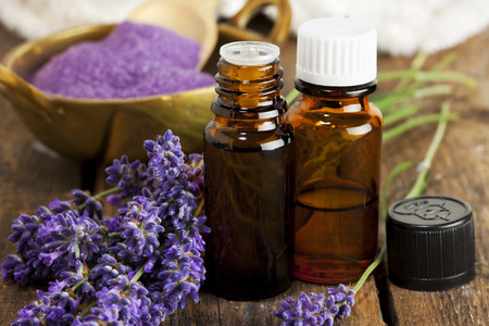 aromatherapy oil: Bottles of aromatherapy essence and bath salt with lavender flowers closeup