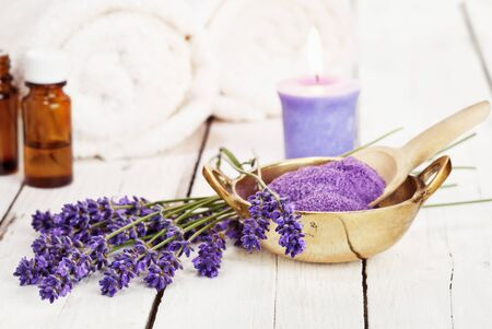 scented candle: lavender flowers, bath salt, massage oil, scented candle and towels on rustic white background, high key image