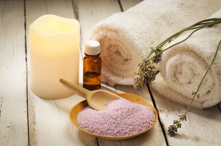 bath salt: spa still life with lavender, bath salt, aromatic oil, candle and towels on wood background