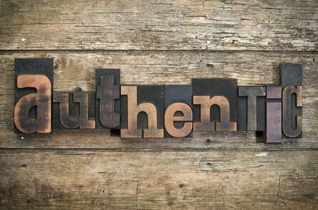 Het woord 'authentieke' geschreven met vintage boekdruk blokken op rustieke houten achtergrond Stockfoto