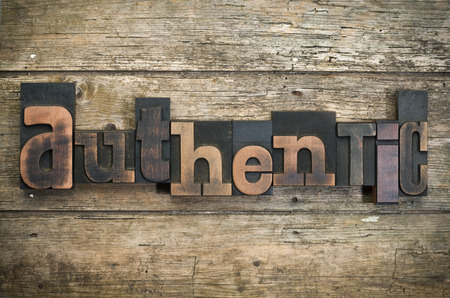 word authentic written with vintage letterpress printing blocks on rustic wood background