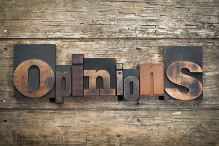 word opinions written with vintage letterpress printing blocks on rustic wood background