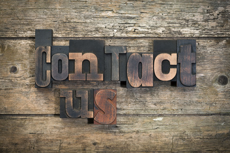 """uitdrukking """"contact"""" geschreven met vintage boekdruk blokken op rustieke houten achtergrond"""