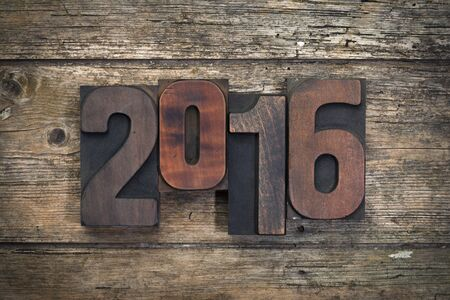 wood block: year 2016 written with vintage letterpress printing blocks on rustic wood background