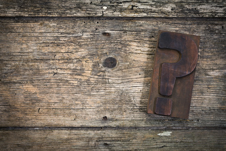 question mark vintage letterpress printing block on rustic wood background, copy space on left side Foto de archivo