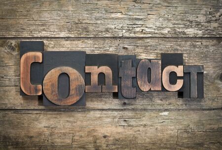 word contact written with vintage letterpress printing blocks on rustic wood background Stock Photo