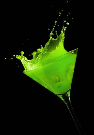 tilted view: ice cube making a splash in green cocktail, black background, tilted view