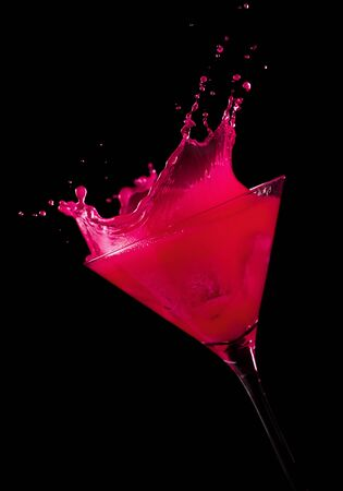 tilted view: ice cube making a splash in pink cocktail, black background, tilted view Stock Photo