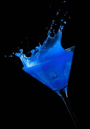 tilted view: ice cube making a splash in blue cocktail, black background, tilted view