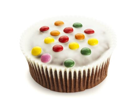 smarties: Cupcake with white chocolate icing and Smarties isolated on white background
