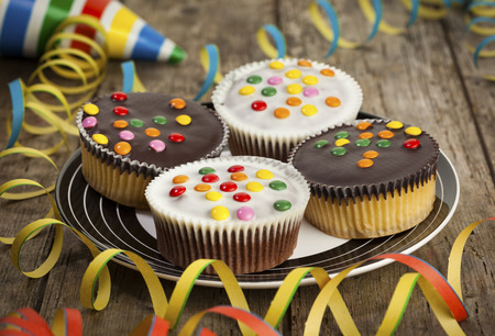 smarties: Cupcakes with chocolate icing and smarties on a plate surrounded by streamers