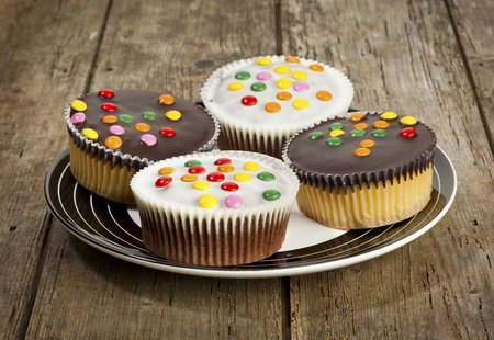 smarties: four cupcakes with dark and white chocolate icing and smarties on a plate Stock Photo