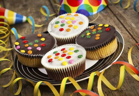 tilted view: four cupcakes with dark and white chocolate icing and smarties on a plate, surrounded by straemers and party hats, tilted view Stock Photo