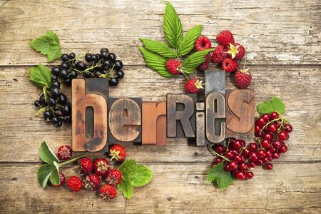 printing block block: berries, word written with vintage letterpress type, surrounded by fresh berry fruits on wooden background