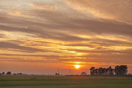 quagmire: Lower Saxony marsh landscape at sunset, wind turbines at horizon Stock Photo