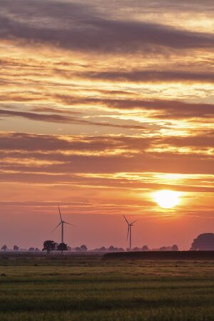 mire: Two wind turbines at northern German bog landscape in sunset Stock Photo