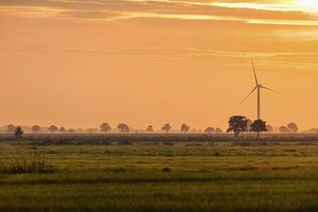 quagmire: Wind turbine at horizon of Northern German marsh landscape at sunset