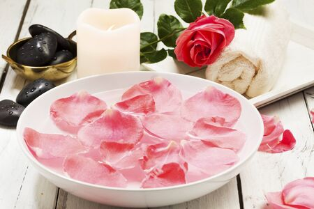 lastone: rose petals in bowl, massage stones, towel, flower and candle Stock Photo