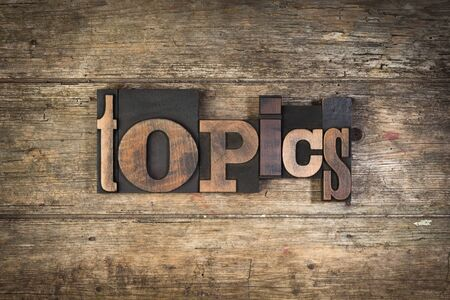 topics: Topics, set with vintage letterpress printing blocks on wooden background