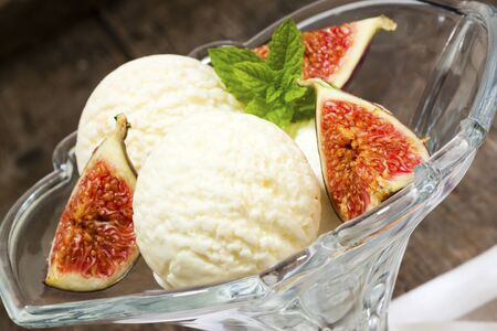 tilted view: Three scoops of vanilla ice cream with fresh figs in glass bowl, tilted view Stock Photo