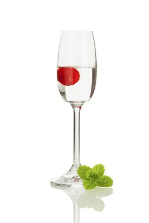 hard liquor: Glass of Himbeergeist with berry isolated on white background, decorated with mint leaves