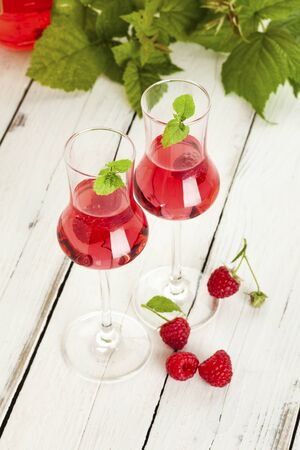 liqueurs: Two glasses of raspberry liqueur, stray berries, leaves in background, on rustic white table Stock Photo