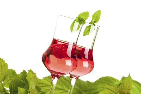 tilted view: Two glasses of raspberry liqueur decorated with peppermint in front of raspberry leaves, tilted view, isolated on white backgrounbd