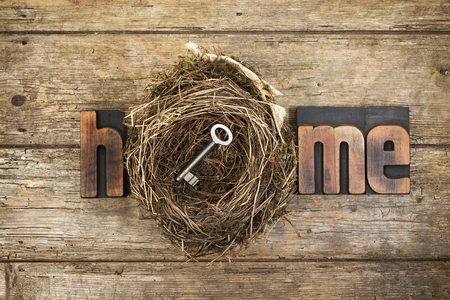 Home, word written with vintage letterpress printing blocks and bird's nest containing a door key on rustic wooden background