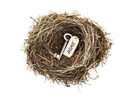 ?real estate?: Clave de la puerta con la etiqueta casa en nido de aves aisladas sobre fondo blanco