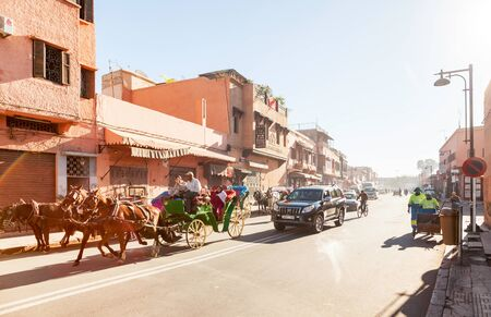 horse drawn: Marrakesh, Morocco: Horse drawn carriages, cars, cyclists and street cleaners on busy street at the Medina
