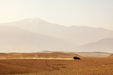 Offroad vehicle driving through Agafay desert, Morocco, Atlas Mountains vanishing in haze