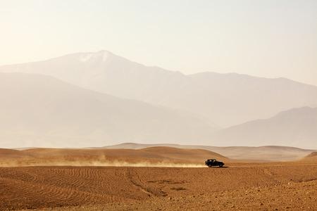 Offroad vehicle driving through Agafay desert, Morocco, Atlas Mountains vanishing in haze