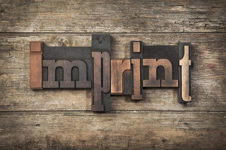 imprint: imprint, word written with vintage letterpress type on rustic wooden abckground