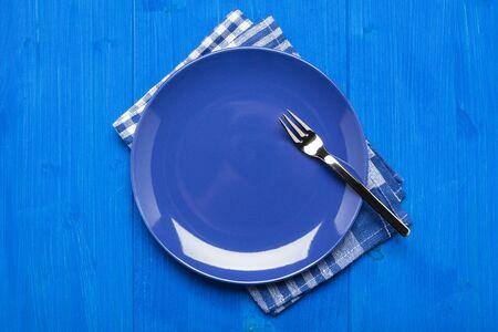 Blauw bord met vork op servet en blauwe tafel