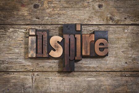 letterpress blocks: inspire, single word set with vintage letterpress printing blocks on rustic wooden background