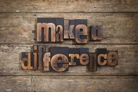 letterpress blocks: make a difference, phrase set with vintage letterpress printing blocks on rustic wooden background Stock Photo