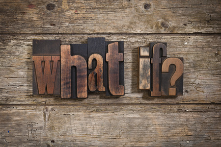 what if: what if, phrase set with vintage letterpress printing blocks on rustic wooden background