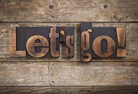 letterpress blocks: lets go, phrase set with vintage letterpress printing blocks on rustic wooden background